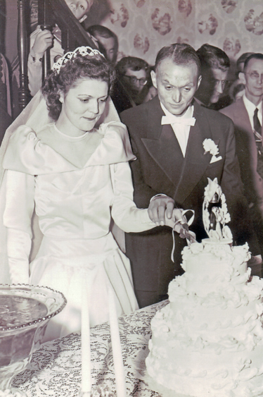 Gerald and Claudene (Ramsey) Johnson, cutting their wedding cake, 6 Nov 1953.